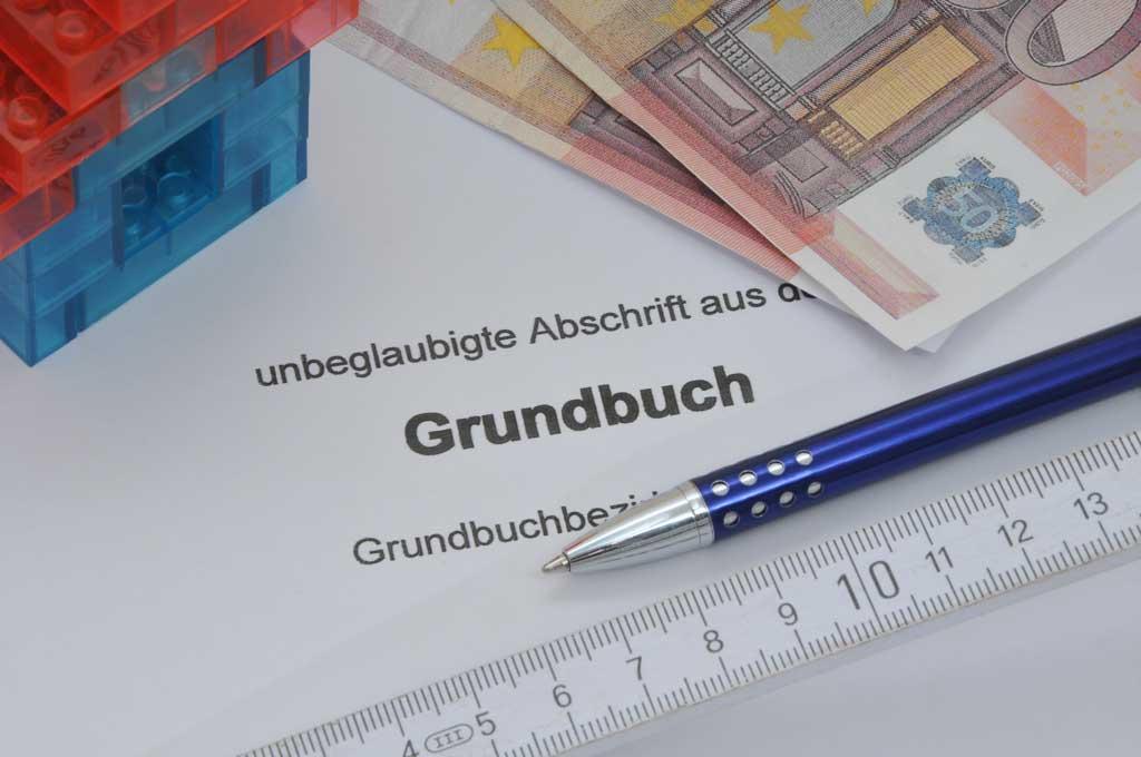 Grundbuch Bestandteile. Auf dem Foto sind das Wort Grundbuch, ein Kugelschreiber, Geldnoten und ein Haus zu sehen.