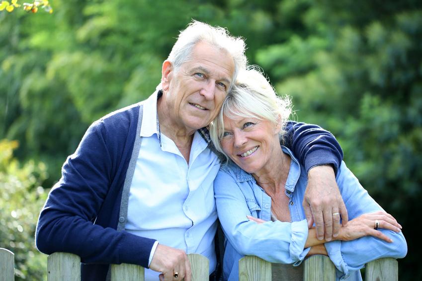 Älteres Ehepaar steht am Zaun im Hof