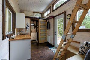 Inneneinrichtung eines Esszimmers und einer Küche in einem winzigen rustikalen Blockhaus.