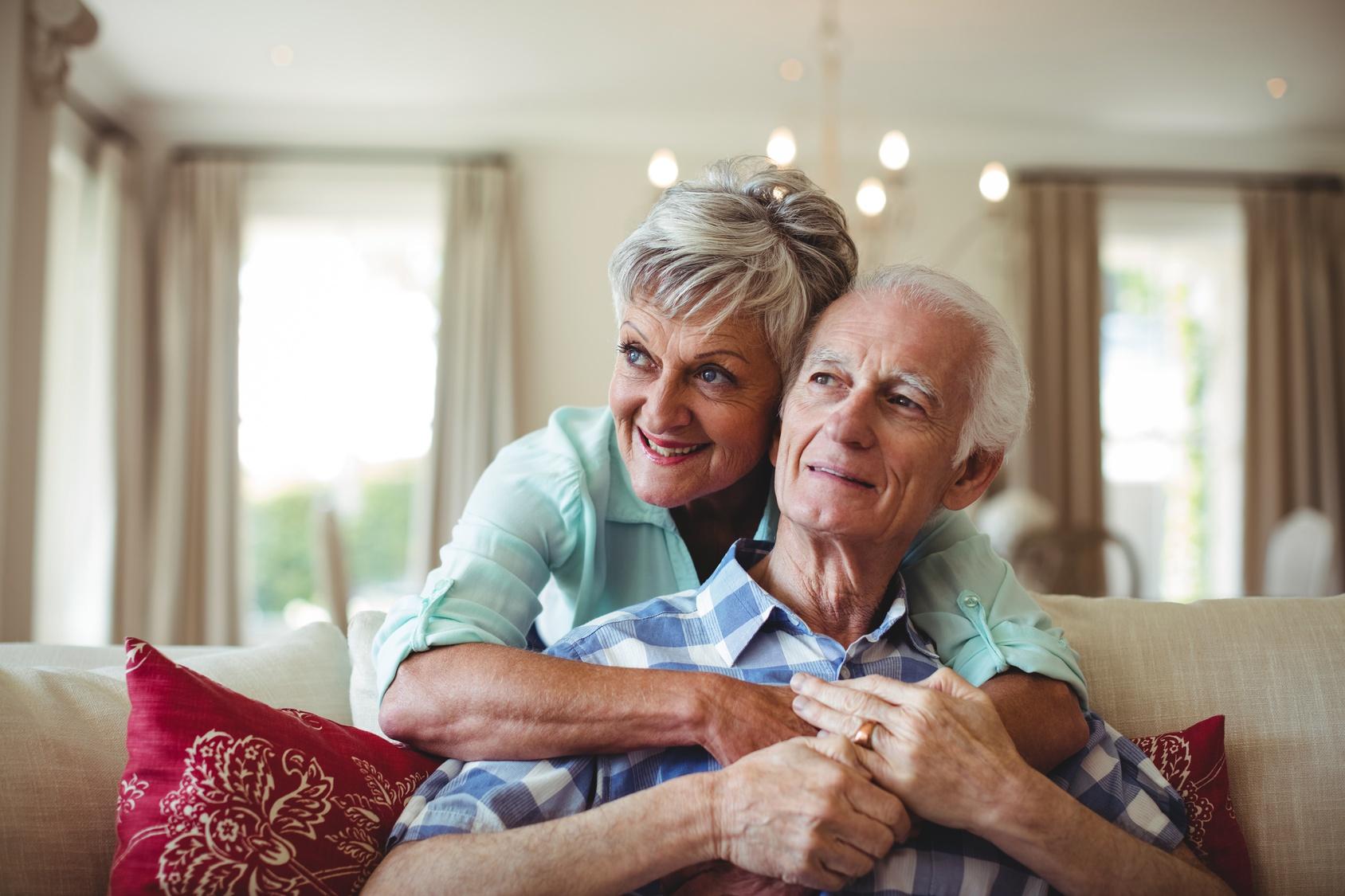 Seniorenpaar entspannt sich auf dem Sofa im Wohnzimmer