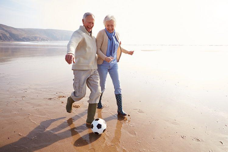 Senior Couple Playing Football On Winter Beach Having Fun