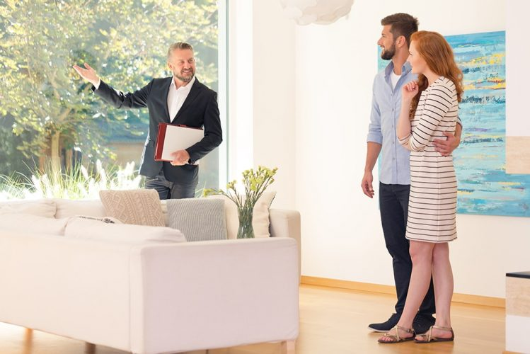 Real estate agent showing home interior for sale to young couple