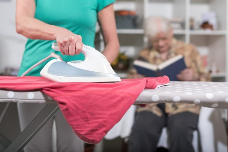 Home helper ironing clothes for elderly woman