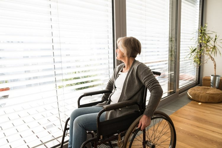 Disabled senior woman in wheelchair at home in her living room, looking out the window.